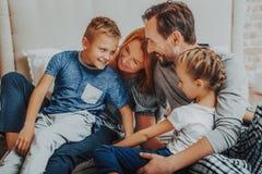 Lyckliga föräldrar och två ungar som tillsammans omfamnar fotografering för bildbyråer