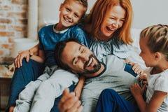 Lyckliga föräldrar och två ungar som tillsammans skrattar arkivbilder