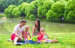 Lyckliga föräldrar och två ungar som utomhus har picknick Royaltyfri Bild