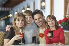 Lyckliga föräldrar och ungar med drinkar på restaurangen arkivbilder