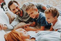 Lyckliga föräldrar och ungar som tillsammans kopplar av i säng arkivfoton
