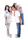 Lyckliga föräldrar som ger deras barn en ridtur på axlarna Arkivbild