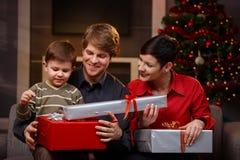Lyckliga föräldrar som ger julgåvor till sonen Royaltyfri Foto