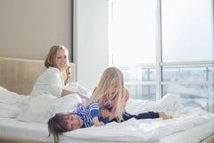 Lyckliga föräldrar som ser skämtsamma barn i sovrum royaltyfria bilder