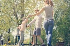 Lyckliga föräldrar som spelar med deras barn i ängen familj Royaltyfri Bild