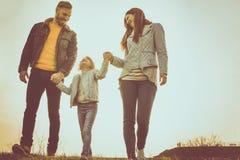 Lyckliga föräldrar som spelar med deras dotter i parkera arkivbilder
