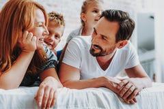 Lyckliga föräldrar som tycker om morgontid med ungar arkivfoto
