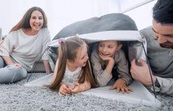Lyckliga föräldrar spelar med barn i ett tält i vardagsrummet royaltyfri fotografi