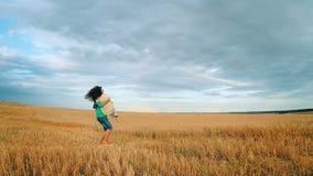 Lyckliga förälskade barnpar har romans och spring till och med ett vetefält i sommar Solnedgång ultrarapid stock video