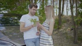 Lyckliga förälskade par tycker sig om, man sitter på huven av bilen lager videofilmer