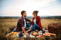 Lyckliga förälskelsepar på picknick i sommarfält royaltyfria bilder