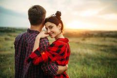 Lyckliga förälskelseparkramar i sommarfält på solnedgången royaltyfri foto