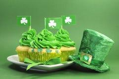 Lyckliga för daggräsplan för St Patricks muffin på grön bakgrund royaltyfria bilder