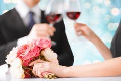 Lyckliga förlovade par med blommor och vinexponeringsglas arkivbilder