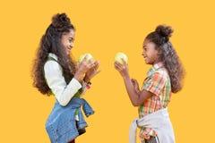 Lyckliga förtjusta systrar som står mitt emot de fotografering för bildbyråer