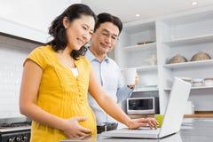 Lyckliga förväntansfulla par genom att använda bärbara datorn Arkivfoton