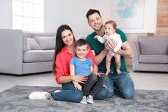 Lyckliga f?r?ldrar och deras gulliga barn som hemma sitter p? golv royaltyfria bilder