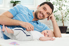 Den lyckliga fadern ligger med en behandla som ett barn Arkivbild