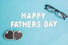 Lyckliga faders dag med svarta exponeringsglas och hjärtor på blå blackgr Arkivfoton