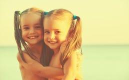Lyckliga familjbarn kopplar samman systrar på stranden Royaltyfri Fotografi