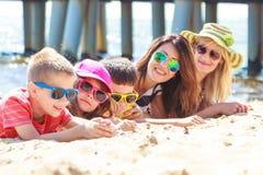 Lyckliga familjkvinnaungar som solbadar på stranden Arkivfoto