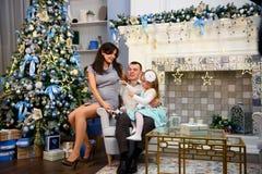 Lyckliga familjpar ger gåvor i vardagsrummet, bak den dekorerade julgranen, ljuset för att ge en hemtrevlig atmosfär royaltyfri bild
