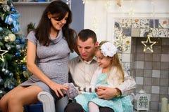 Lyckliga familjpar ger gåvor i vardagsrummet, bak den dekorerade julgranen, ljuset för att ge en hemtrevlig atmosfär royaltyfria foton