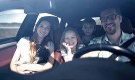 Lyckliga familjritter i bilen royaltyfri foto