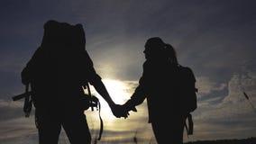 Lyckliga familjturister som g?r rymma handkonturn p? solnedg?ngen begrepp f?r fotvandrareteamworklopp Man- och kvinnapar arkivfilmer