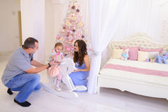 Lyckliga familjutbytesgåvor i rymligt sovrum tänder på backgro Royaltyfria Bilder