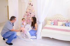 Lyckliga familjutbytesgåvor i rymligt sovrum tänder på backgro Royaltyfri Bild