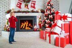 Lyckliga ferier! Det gulliga lilla barnet grundar många gåvor under julgranen Royaltyfri Fotografi