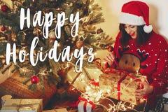 Lyckliga ferier smsar, den lyckliga kvinnan i ask för gåvan för den santa hattöppningen a Fotografering för Bildbyråer