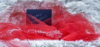 Lyckliga ferier smsar på svart kort med röd tyll och pärlor på wh Arkivfoto