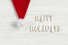 Lyckliga ferier smsar tecknet på den julsanta hatten på vitt lantligt Arkivfoton