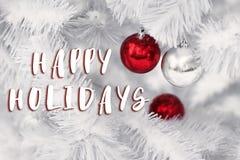 Lyckliga ferier smsar tecknet på röda och silverprydnadbollar på whi Royaltyfri Fotografi