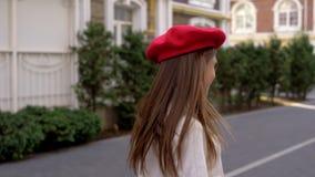 Lyckliga flickaaktiviteter i staden i en röd basker lager videofilmer