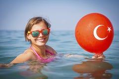 Lyckliga flickabad i havsvatten Semester i Turkiet Turkisk flagga på ballongen Le flickan på havet Arkivbild