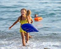 Lyckliga flickakörningar ut ur havet på kust Royaltyfri Fotografi