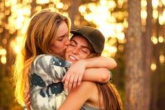 Lyckliga flickavänner som kramar i en skog på solnedgången Arkivbild