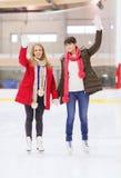 Lyckliga flickavänner som vinkar händer på att åka skridskor isbanan Arkivbild