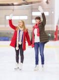 Lyckliga flickavänner som vinkar händer på att åka skridskor isbanan Arkivfoton