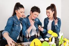 Lyckliga flickor firar påskferie, och spela med målarfärgägg dekorera på skrivbordet Fotografering för Bildbyråer