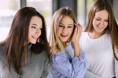 Lyckliga flickor grupperar ståenden som ser, shoppar fönstret Royaltyfria Bilder