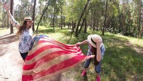 Lyckliga flickor har gyckel och dansen med USA flaggan, oberoende dag av Amerika stock video