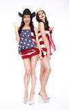 Lyckliga flickor, i att posera för hattar och för amerikanska flaggan arkivfoton