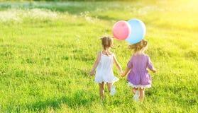 Lyckliga flickor kopplar samman systrar med ballonger i sommarfält på naturen Royaltyfri Bild