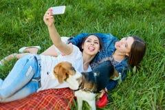 Lyckliga flickor med deras hundbeaglesammanträde i gräsplan parkerar och makien Fotografering för Bildbyråer