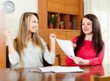Lyckliga flickor med dokument på tabellen Arkivbild
