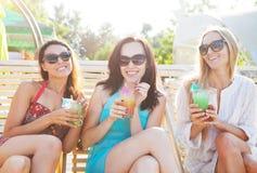 Lyckliga flickor med drycker nära pölen fotografering för bildbyråer